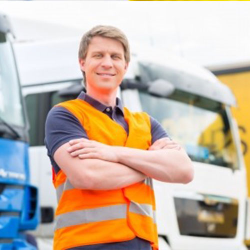 A portrait of a happy lorry driver standing in front of two lorries.