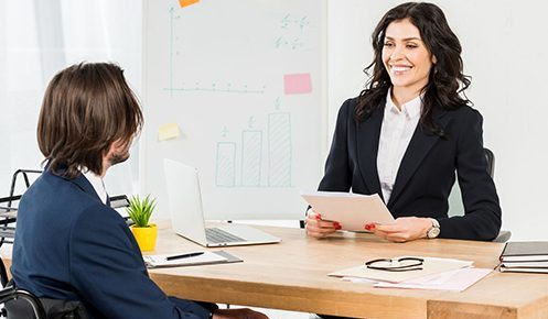A happy business woman, holding a document, having a meeting with a man at a desk.
