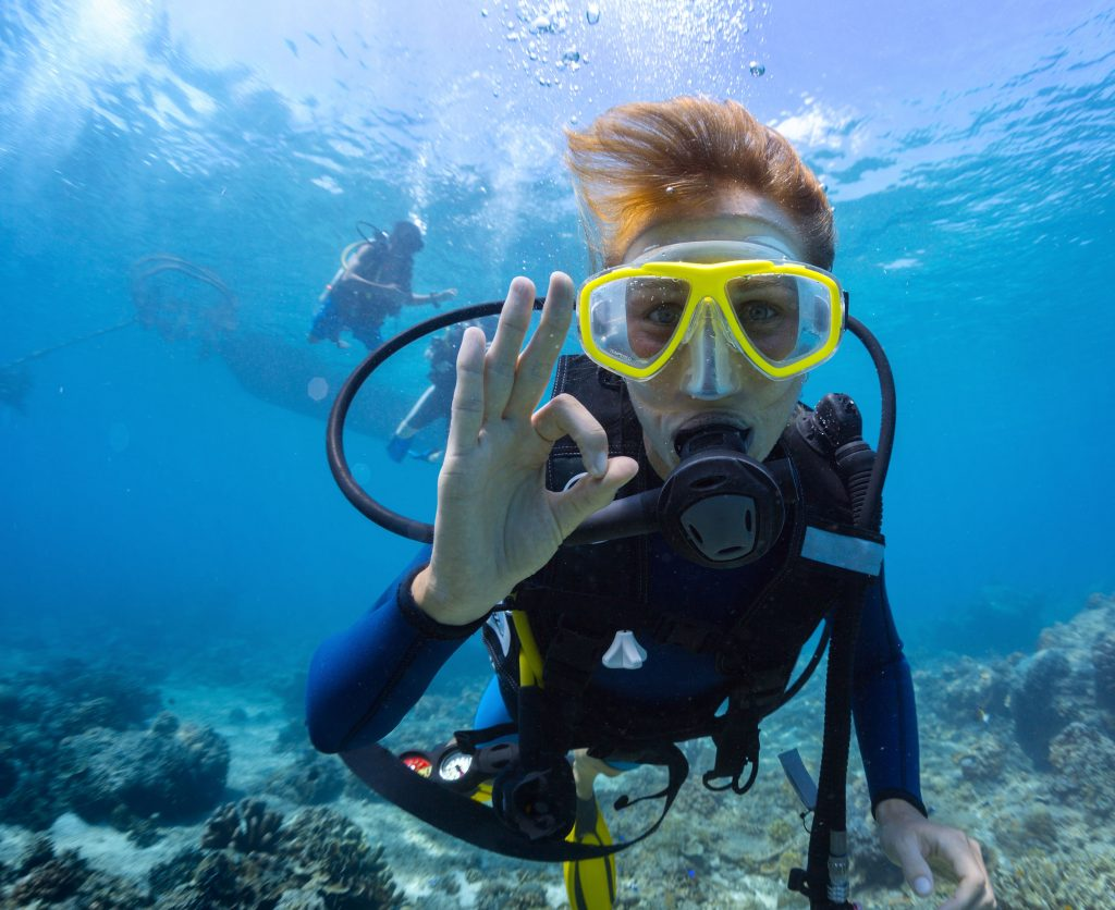 A picture of a scuba diver swimming along the sea floor next to coral