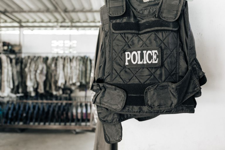 A close up image of a black police vest, with more uniform in the background.
