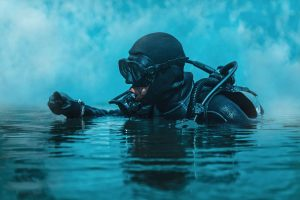 A navy seal in scuba equipment above the water